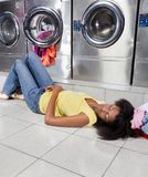 Woman Sleeping On Floor At Laundry Stock Images
