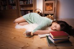 Woman sleeping in front of fireplace Royalty Free Stock Photography