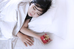 Woman sleeping with a gift box Royalty Free Stock Photos