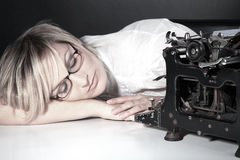 Woman sleeping with glasses and old typewriter Royalty Free Stock Images
