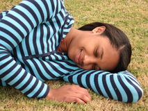 Woman sleeping on grass. Young smiling black woman sleeping on grass outdoors Royalty Free Stock Images