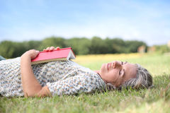 Woman sleeping in grass with book opened on she Stock Image