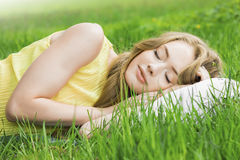 Woman sleeping on grass. Young woman sleeping on white pillow in fresh spring grass stock photography