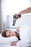Woman sleeping while the gun aimed at her. Young woman sleeping while the gun aimed at her Royalty Free Stock Image