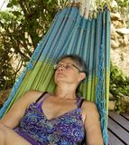 Woman sleeping in a Hammock. Woman outdoors sleeping in a Hammock with green tree in the background stock image