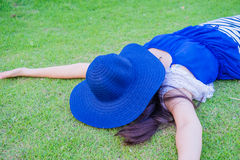 Woman sleeping. With hat over face her on lawn Stock Image