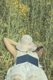 Woman sleeping with hat over face her on rape meadow.  Royalty Free Stock Images