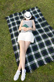 Woman sleeping with a hat over her face in a park Royalty Free Stock Images
