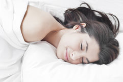 Woman sleeping and having nice dream. Woman sleeping, dreaming nice smiling in the late morning on white sheets Royalty Free Stock Image