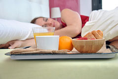 Woman sleeping on her bed with a breakfast. At his side Stock Photo