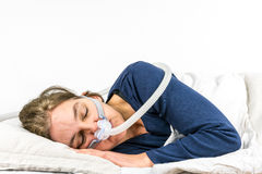 Woman sleeping on her side with CPAP, sleep apnea treatment.