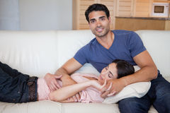 Woman sleeping while his boyfriend is posing. In their living room Royalty Free Stock Photography