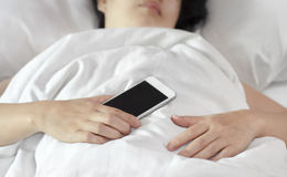 Woman sleeping and holding a mobile phone. stock photo