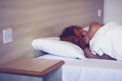 Woman sleeping in hotel room Stock Photography