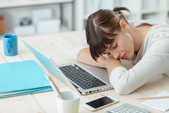 Woman sleeping on the job. Young tired woman at office desk sleeping with eyes closed, sleep deprivation and stressful life concept Royalty Free Stock Photo