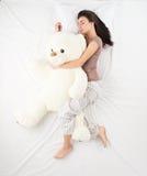 Woman sleeping with large teddy bear royalty free stock photos