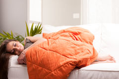 Woman sleeping like a baby. In her very comfortable living room on her white sofa under an orange quilt Stock Photography