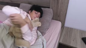 Woman sleeping and looking for soft toy stock video footage