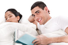 Woman sleeping and man happily reading book in bed. Over white background Royalty Free Stock Photos