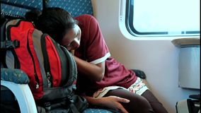 Woman sleeping in a moving train. Woman sleeping on her backpack in a moving train stock video