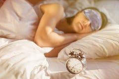 Woman sleeping next to alarm clock royalty free stock image