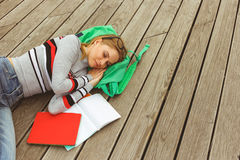 Woman sleeping next to open notebook on wooden surface Royalty Free Stock Images