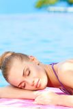 Woman sleeping next to swimming pool Stock Images