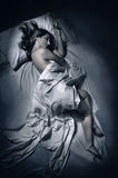 Woman sleeping at night in bed Stock Photo