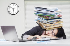 Woman sleeping in office with paperwork on head Royalty Free Stock Image