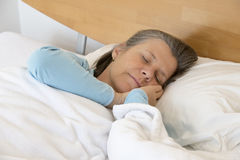 Woman sleeping. Older woman lying in bed and sleeping peacefully Royalty Free Stock Images
