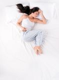 Woman sleeping in open fetal position. Beautiful young woman sleeping in open fetal position on white bed stock photography