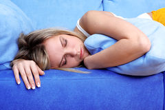 Woman sleeping at pillows in sofa Royalty Free Stock Image