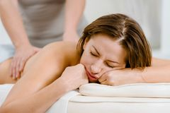 Woman sleeping on procedure. Relaxed woman sleeping while having back massage procedure royalty free stock photos
