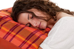 Woman Sleeping in a Red Pillow. Young woman sleeping on a red pillow, in a white background Royalty Free Stock Photography