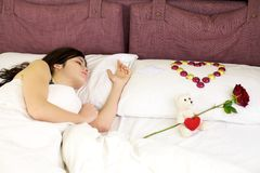 Woman sleeping with San Valentine gifts. Romantic gifts for beautiful woman, heart of chocolate, rose and love message Stock Image
