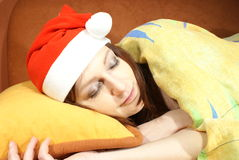Woman sleeping with Santa hat. A closeup view of a young woman in bed, sleeping on a yellow pillow wearing a red Santa hat Stock Image