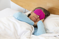Woman sleeping with sleep mask. Older woman lying in bed and sleeping peacefully with a sleep mask on Stock Photos