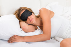 Woman Sleeping With Sleep Mask. Young Woman Sleeping With Sleep Mask In Bed royalty free stock photos