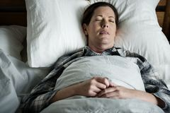 A woman sleeping soundly on bed Stock Photos