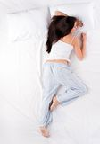 Woman sleeping in starfish position Royalty Free Stock Images