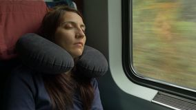 Woman Sleeping in Train. Woman is sleeping in the car while travelling by train and having an inflatable neck pillow for sleep stock footage