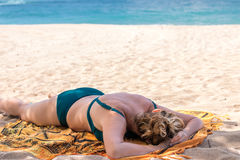 Woman sleeping on the tropical beach Nusa Dua, Bali island, Indonesia. royalty free stock image