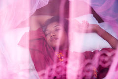 Woman sleeping under a mosquito net Royalty Free Stock Photos