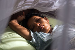 Woman sleeping under a mosquito net Stock Photos