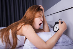 Woman sleeping and wake up to turn off the alarm clock in mornin Stock Photography