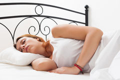 Woman is sleeping on a white pillow in bed at home Royalty Free Stock Images