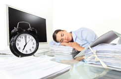 Woman sleeping on work in the office desk with clock Royalty Free Stock Image