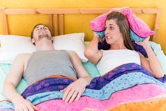 Woman is sleepless and angry because of her snoring husband. In bed Royalty Free Stock Images
