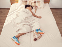 Woman sleeps in bed with her running shoes on Royalty Free Stock Images