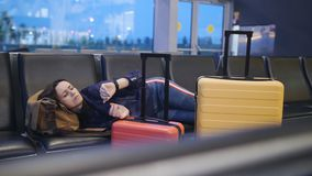 A woman sleeps on a bench in an airport terminal building. Waiting for a long transfer on a flight